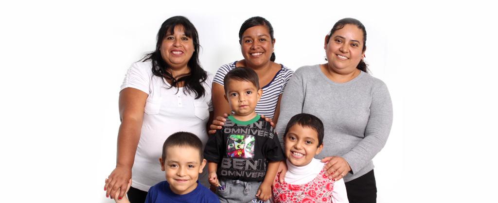 Tres mujeres, cada una con sus hijos; todos sonríen.
