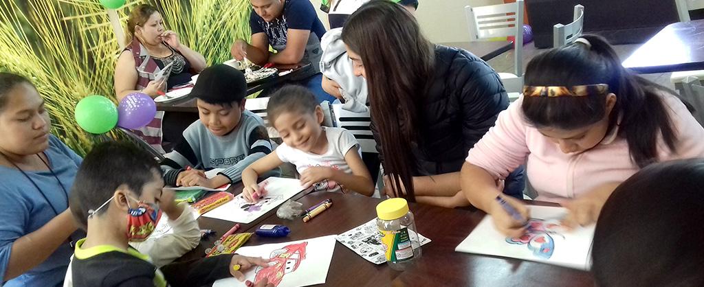 En una mesa hay varios niños colorando; en otra mesa, hay una pareja comiendo.